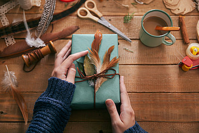 Woman decorating Christmas present with leaf and feathers, close-up - p300m1192366 by Retales Botijero