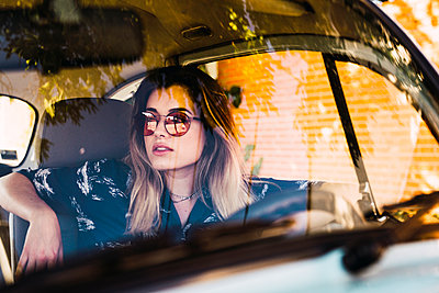 Young woman wearing sunglasses sitting in a car - p300m2023476 by Kike Arnaiz
