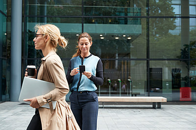 Woman holding laptop while walking with businesswoman using mobile phone in background - p300m2226419 by Pete Muller