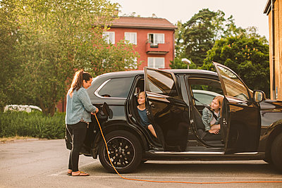 Girls looking at smiling mother charging electric car at station - p426m2072402 by Maskot