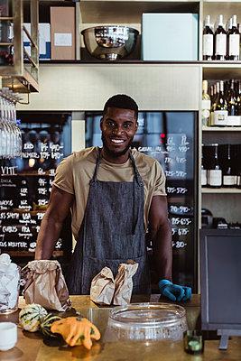 Portrait of smiling male entrepreneur standing in delicatessen shop - p426m2270616 by Maskot