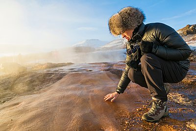 Woman touching the ground by The Great Geysir, a geyser that lies in the Haukadalur valley on the slopes of Laugarfjall hill, South West Iceland - p429m1105663 by dotdotred