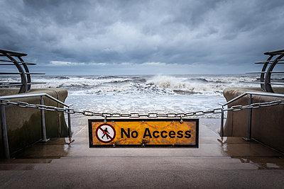 """""""No access"""" sign at stormy beach - p429m800855f by Dan Brownsword"""