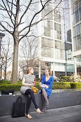 Businesswomen sitting on wall for coffee break - p429m803587f by Liam Norris