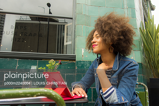 Smiling thoughtful businesswoman looking away at sidewalk cafe - p300m2240004 by LOUIS CHRISTIAN