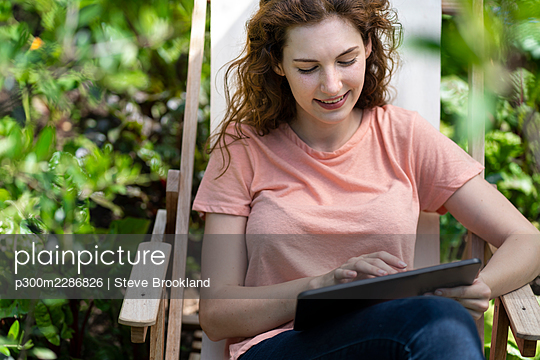 Young woman using digital tablet on chair in garden - p300m2286826 by Steve Brookland