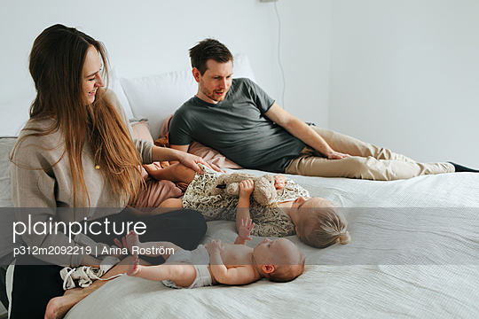 Family on bed - p312m2092219 by Anna Roström