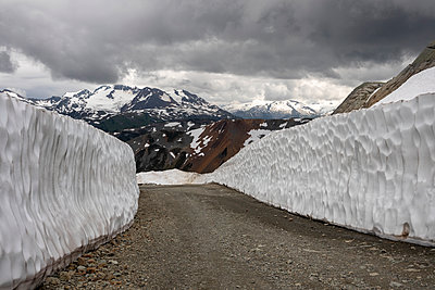 High snowwalls line a mountain road backdropped by mountains on Whistler Blackcomb Ski Resort in Canada. - p1166m2147480 by Cavan Images