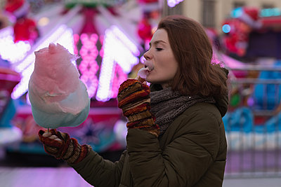 Woman in winter clothing having candy floss in amusement park - p1315m1566479 by Wavebreak