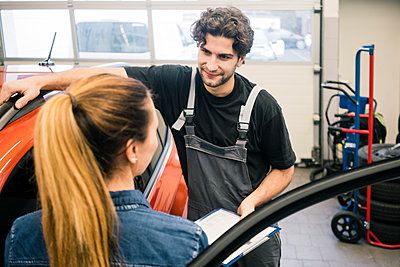 Car mechanic talking to client in workshop - p300m2166831 by Robijn Page