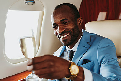 Smiling businessman with champagne looking away while traveling in airplane - p300m2256396 by OneInchPunch
