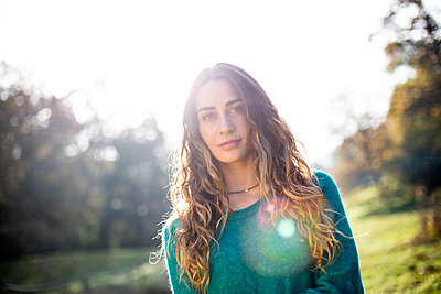 Young woman with long hair in a park - p975m2222100 by Hayden Verry
