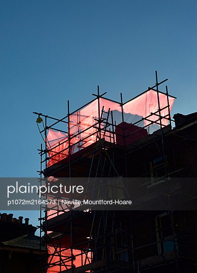 Silhouette of building scaffolding with red covering - p1072m2164573 by Neville Mountford-Hoare