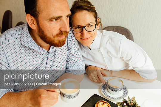 Couple drinking cappuccino while sitting at table in cafe - p1166m2207903 by Cavan Images