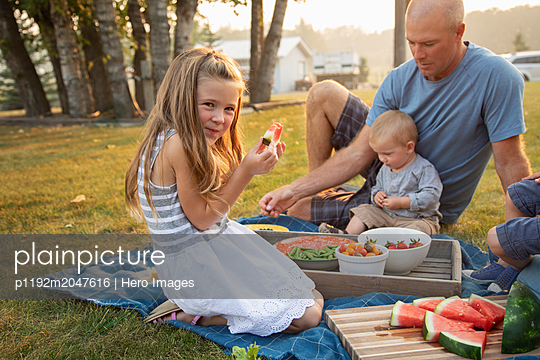 Portrait happy girl eating watermelon, enjoying picnic with family - p1192m2047616 by Hero Images
