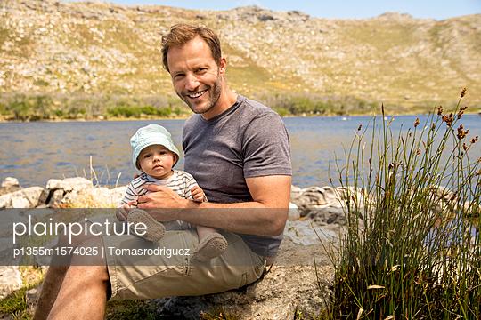 Vater und Baby am Seeufer - p1355m1574025 von Tomasrodriguez