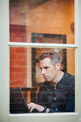 Mann in einem Cafe arbeitet am Laptop  - p1057m1526432 von Stephen Shepherd