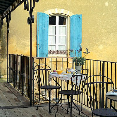"""""""Metal bistro table set for two on wooden balcony with simple metal railing; blue shutters in background"""" - p1183m995830 by Hausmann, Jose-Luis"""