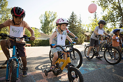 Kids racing bikes at summer neighborhood block party - p1192m2017133 by Hero Images