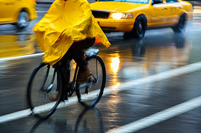 Cyclist in yellow poncho during rain in New York City, USA - p1427m2077623 by Tetra Images