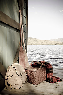 Oars and picnic supplies by lake - p1427m2186444 by Chris Hackett
