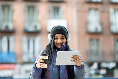 Young woman listening music through digital tablet while holding reusable cup in city - p300m2252617 by Jose Carlos Ichiro