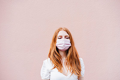 portrait of beautiful redhair woman over pink wall weraring face mask, Madrid, Spain - p300m2274012 von Eva Blanco