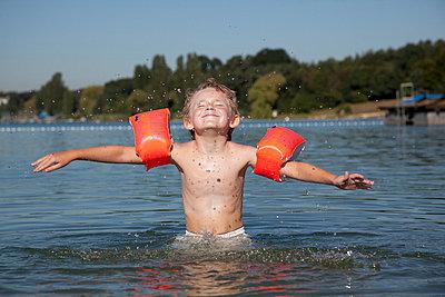 7-jähriger Junge planscht im See - p731m698998 von Volker Ramspott