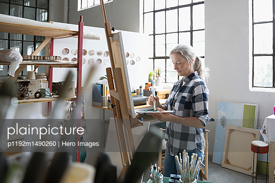 Female painter with palette painting at canvas in art studio - p1192m1490260 by Hero Images