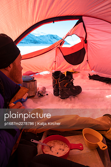 Man having breakfast in tent while looking at winter landscape outside - p1687m2278786 by Katja Kircher