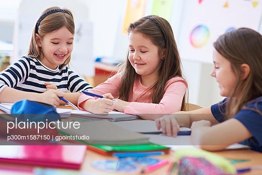 Happy schoolgirls working together in class - p300m1587150 von gpointstudio