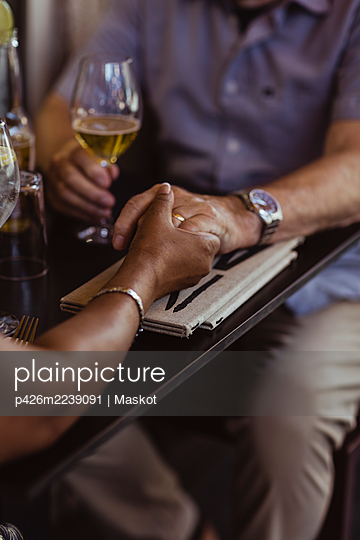 Cropped image of couple holding hands over table in cafe - p426m2239091 by Maskot
