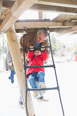 Grandfather playing with grandson on playground ladder - p1023m2161193 by Tom Merton