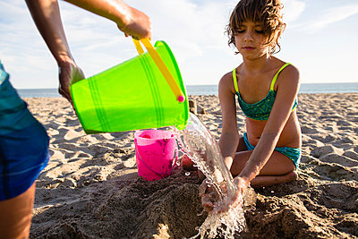 Boy pouring water on sister's hands while making sand castle at beach - p1166m1182986 by Cavan Images