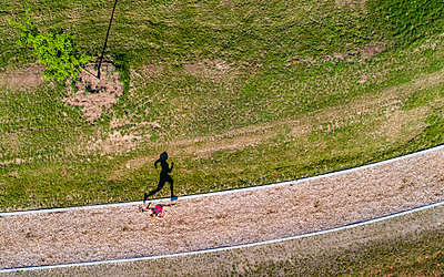 Aerial view of female jogger on woodchip trail - p300m2005376 by Stefan Schurr