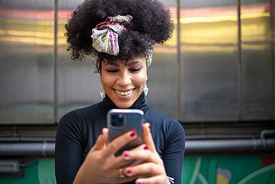 Happy fashionable young woman using mobile phone against wall - p300m2242631 by Ignacio Ferrándiz Roig