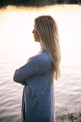 Blond woman with arms crossed on the banks of the Alster - p788m2128832 by Lisa Krechting