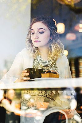 View through coffee shop window of woman with coffee - p924m1174869 by Lena Mirisola