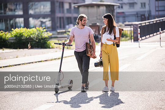 Young couple with electric scooter walking on the street - p300m2132583 by Uwe Umstätter