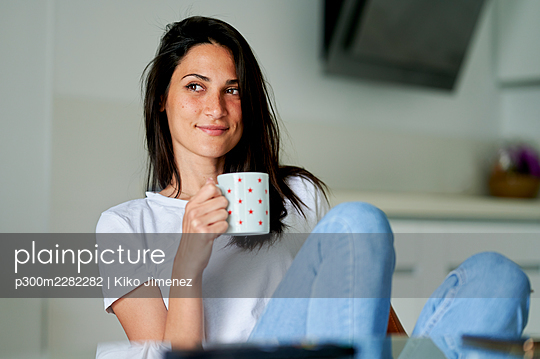 Spain, Andalusia, Jerez, smiling woman with cup at home. - p300m2282282 von Kiko Jimenez