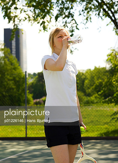Young woman holding tennis racquet drinking water
