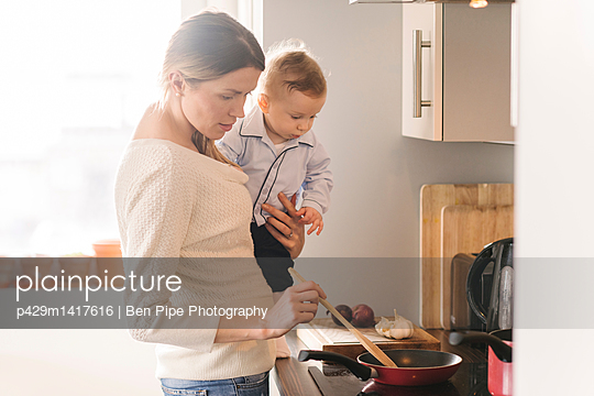 Mother cooking and carrying baby in arms - p429m1417616 by Ben Pipe Photography