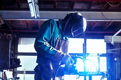 Side view of welder welding in workshop - p1166m1209426 by Cavan Images