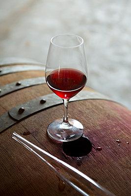 Glass of red wine on a barrel - p1216m2183672 von Céleste Manet