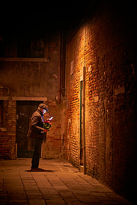 Man with bunch of roses at night - p1312m2054964 by Axel Killian
