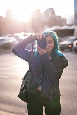 Stylish woman photographing with camera in city street - p1315m1566175 by Wavebreak