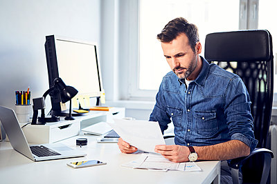Man reading document at desk in office - p300m1567747 by Bartek Szewczyk