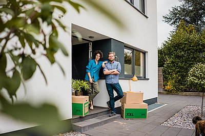 Couple standing at house entrance with cardboard boxes - p300m2080313 von Joseffson