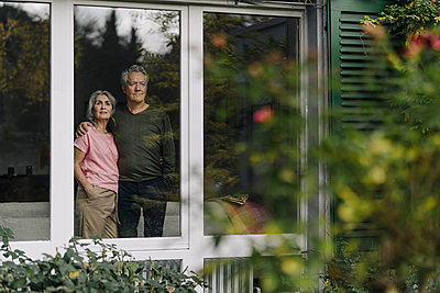 Senior couple behind windowpane of their home looking out - p300m2156223 by Gustafsson