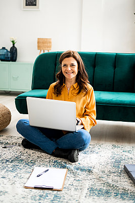 Smiling woman with laptop sitting on floor at sofa in living room - p300m2265373 by Giorgio Fochesato